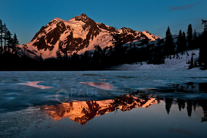 © Paul Conrad/Pablo Conrad Photography -  Mount Shuksan is reflected in a thawing Picture Lake as it is lit by the setting Sun on Saturday June, 22, 2013, while the super perigee Moon begins its ascent into the sky.