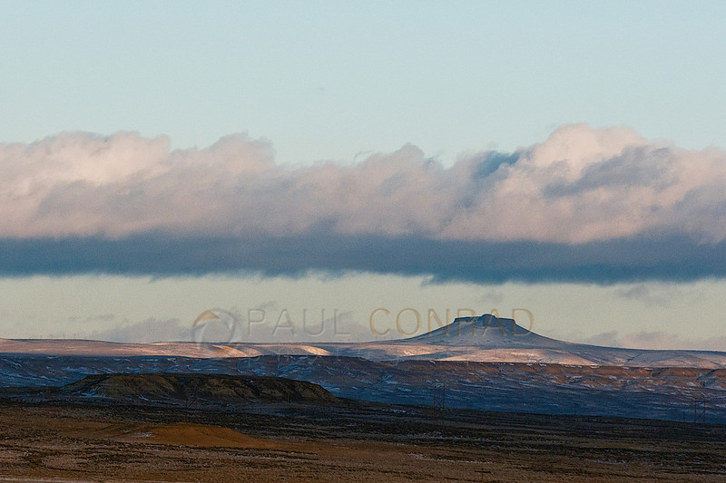 © Paul Conrad/ Pablo Conrad Photography - Landscapes from the backseat: A distant butte covered by incoming storm clouds while driving along Interstate 80 in southwest Wyoming.