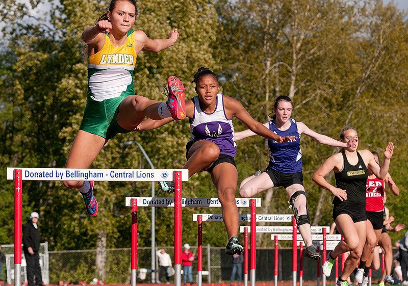 © Paul Conrad/ Pablo Conrad Photography - Lynden's Hannah Hommes, left, Anacortes' Lexia Hall, and Nooksack Valley's Alex Parson trail in Section 2 of the Girls 300m Hurdles during the NWC track & field meet at Civic Field and Stadium in Bellingham, Wash., on Friday April 25, 2-14.