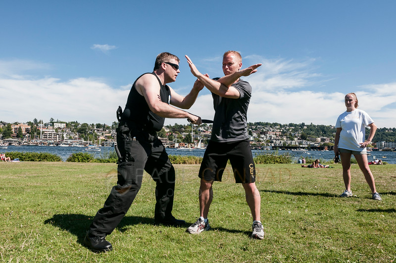 © Paul Conrad/Pablo Conrad Photography - Stephanie, right, watches Arjhan David Brown, left, and Sifu Cory Walken show an incorrect way to block a knife attack as they teach proper knife fighting techniques at Gasworks Park in Seattle, Wash.