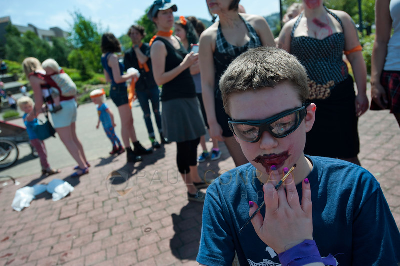 © Paul Conrad/The Bellingham Herald - Zane Rieksts, 13, of Bellingham, gets turned into a zombie by make-up artist Stephanie Matteson during the fifth annual Zombies vs. Survivors as others wait their turn at Maritime Heritage Park on Saturday  May 31, 2014, in Bellingham, Wash.
