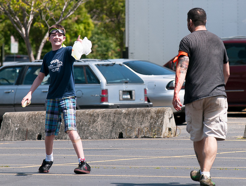 "© Paul Conrad/The Bellingham Herald - ""Survivor"" Zane Rieksts, 13, of Bellingham, warns ""Zombie"" Bill Nupcharoen to stay back before pelting him with a water balloon during the fifth annual Zombies vs. Survivors in downtown Bellingham on Saturday  May 31, 2014, in Bellingham, Wash. Rieksts was caught and converted into a zombie."