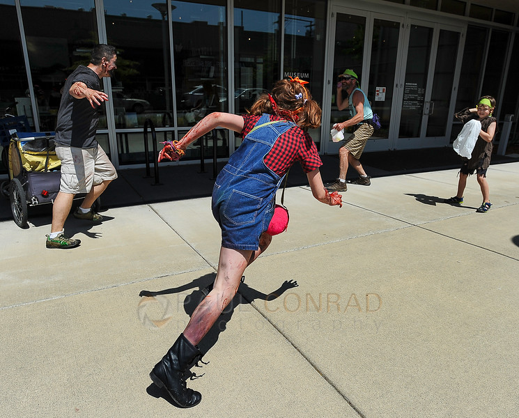 © Paul Conrad/The Bellingham Herald - Bill Nupcharoen, left, of Bellingham and his daughter Rylie, 12 in overalls, attack survivors during the  fifth annual Zombies vs. Survivors on downtown Bellingham on Saturday  May 31, 2014, in Bellingham, Wash.