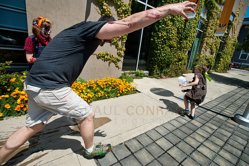 © Paul Conrad/The Bellingham Herald - Frozen after being hit with a water balloon, Rylie Nupcharoen, left, watches as her father Bill Nupcharoen, attacks a little boy during the  fifth annual Zombies vs. Survivors on downtown Bellingham on Saturday  May 31, 2014, in Bellingham, Wash.