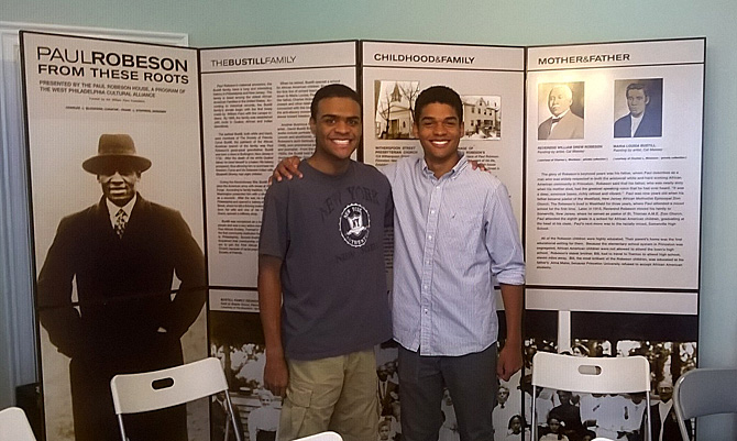 Students pose with each other and a picture of Paul Robeson on one of the historical panels behind them.