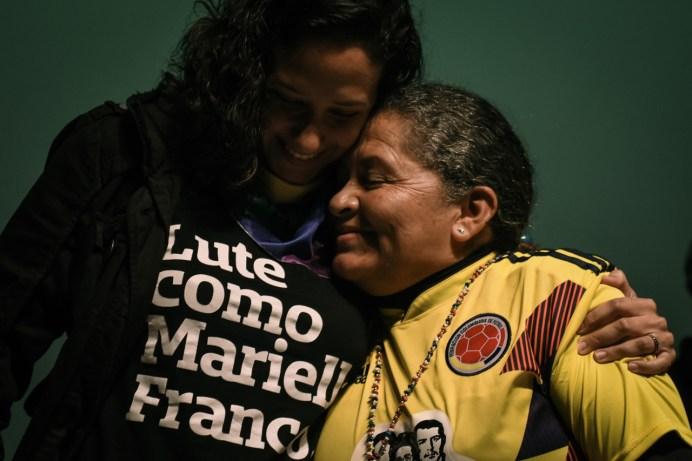 Monica Benicio, compañera de Marielle Franco, abrazada de una madre de víctimas de violencia estatal en Colombia.