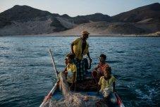 Shafai (centro) conduce un bote cerca de la costa en busca de bancos de peces para pescar el 9 de mayo de 2018 en Fugum, Yemen. Foto: Alex Kay Potter.