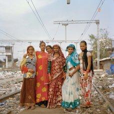 """Las """"hijas"""" de Radhika posan para un retrato cerca de su asentamiento compartido fuera de la estación de tren Mahim en Mumbai, India. La comunidad hijra en Mumbai es predominantemente jerárquica, donde los hijras más experimentados y maduros, como Radhika, actúan como guardianes y superiores a los hijras más jóvenes. Foto: Sara Hylton."""