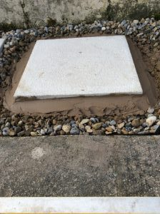 Stepping stone paving slab with cement hunched up the side of the slab to help stop it moving