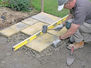 Tap down paving slabs gently with a rubber mallet