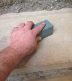 Stone slabs being cleaned with a carborundum sanding and dirt removal stone
