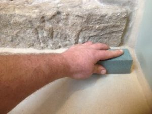 Using a carborundum sanding stone to remove dirt from stone paving slabs