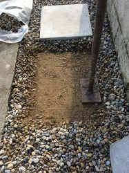 We start by laying the two slabs at either end of our gravel path. First remove the gravel where the stepping stone will be laid then compact the area down to firm the surface.