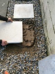 Place a shovel full of motar mix onto the cleared gravel area and even out the mix with a trowel to the size of the stepping stone. Then place the slab on top of the mix.