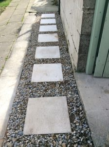 Once you have laid all the slabs we need to remove the line pins and replace any gravel around the stepping stones we have laid. You can gently push some of the stones into the cement to help hide the cement. Finish by cleaning up any mess and don't allow anybody to walk on the slabs for 24 hours.