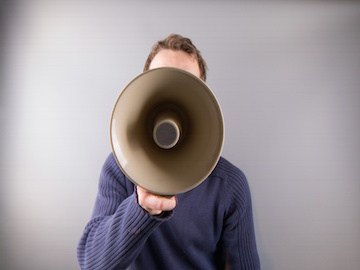 man wearing a blue jumper is holding a megaphone that is obscuring his face