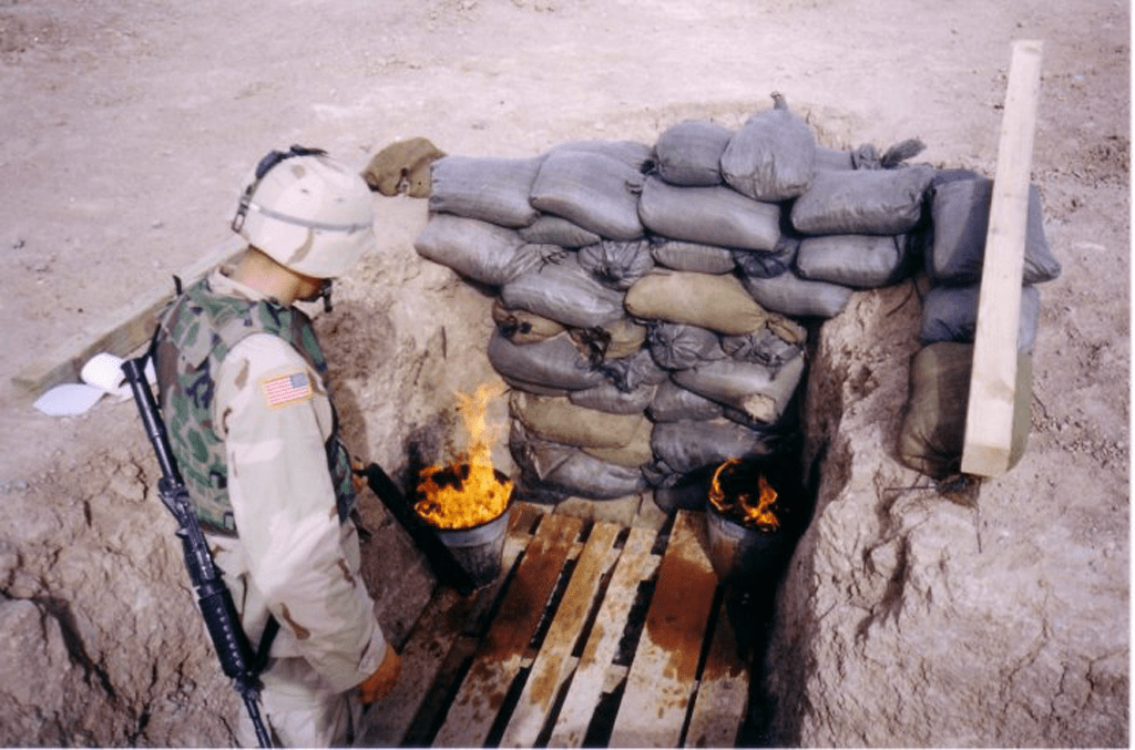 Burning open pit toilets in Kandahar, Afghanistan in 2002. Photo by Timothy Aponte.
