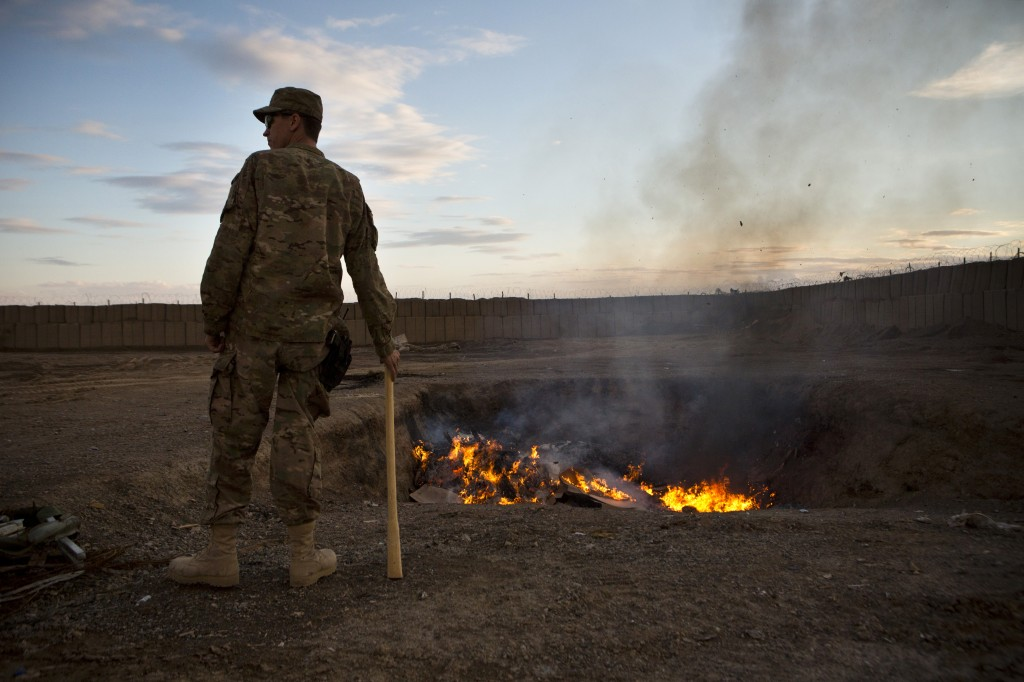 A U.S. Army soldier watches bottled water that had gone bad burn in a burn-pit at Forward Operating Base Azzizulah in Maiwand District, Kandahar Province, Afghanistan, February 4, 2013. Photo by Andrew Burton/Reuters