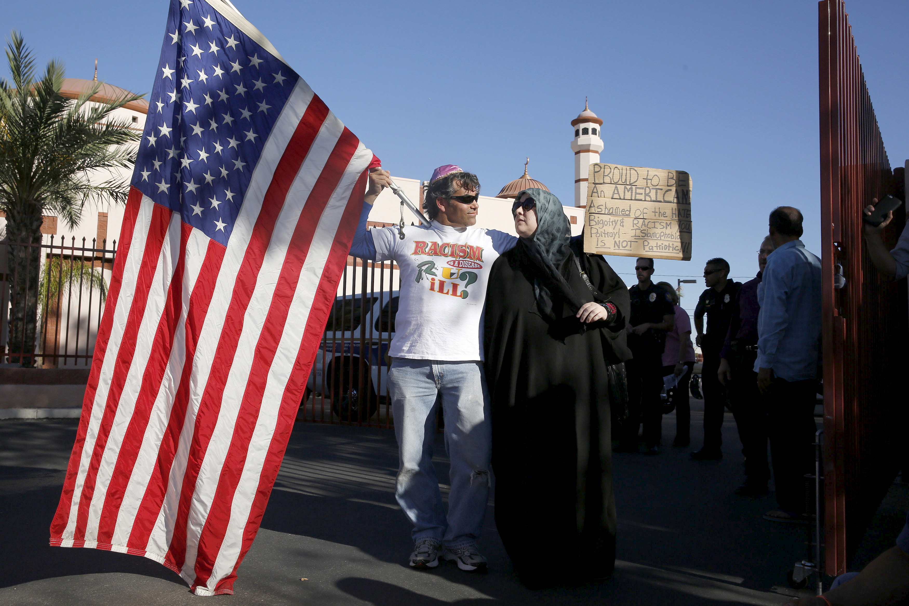 """Two demonstrators stand in front of the Islamic Community Center to oppose the """"Freedom of Speech Rally Round II"""" across the street in Phoenix, Arizona May 29, 2015. Photo by Nancy Wiechec/Reuters."""