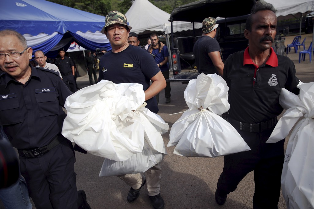 Forensic policemen carry body bags with human remains found at the site of human trafficking camps in the jungle close the Thailand border after they brought them to a police camp near Wang Kelian in northern Malaysia on May 25. Malaysian authorities have found 139 graves, and signs of torture, in more than two dozen squalid human trafficking camps suspected to have been used by gangs smuggling migrants across the border with Thailand, the country's police chief said on Monday. Photo by Damir Sagolj/Reuters