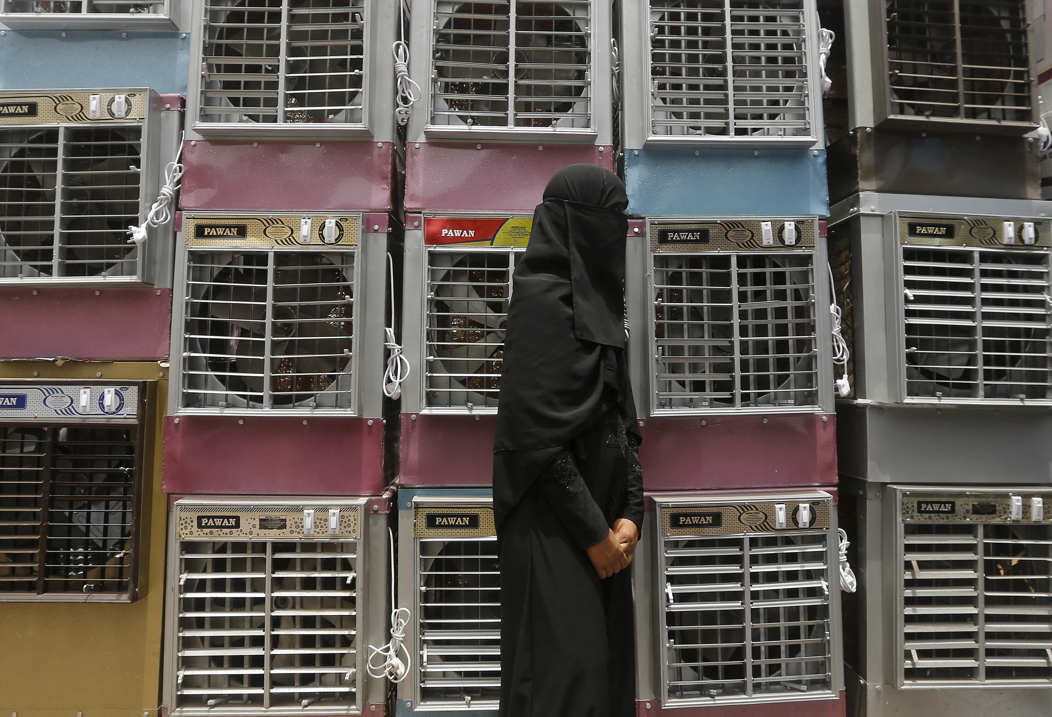 A customer stands beside stacked air coolers kept for sale at a shop in New Delhi, India, May 28, 2015. Photo by Adnan Abidi/Reuters
