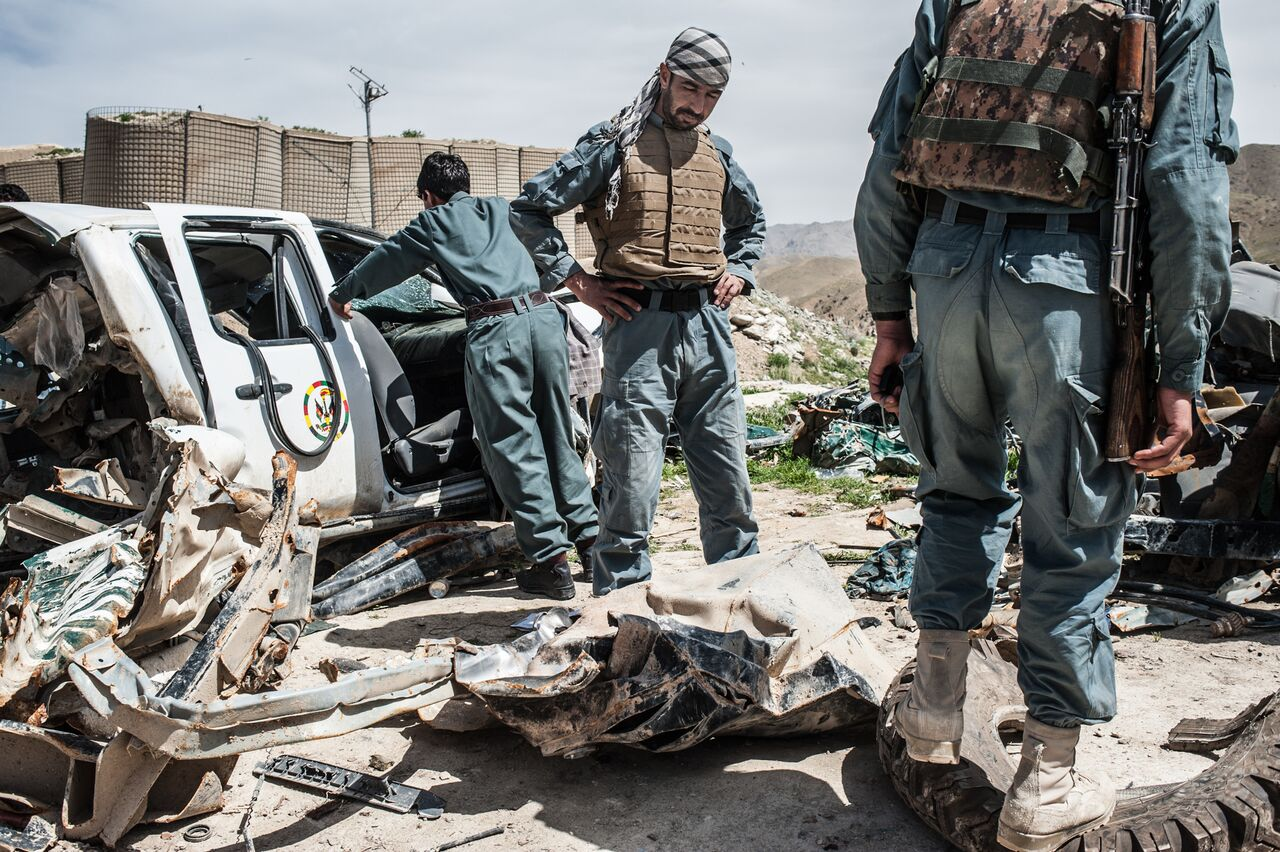 Afghan police officers in Zabul's Arghandab District inspect the damage to two police vehicles that were destroyed by improvised explosive devices. Photo by Ben Brody/The GroundTruth Project