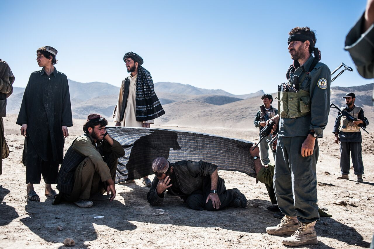 Surrounded by Afghan police and neighbors, a man injured by an explosive device cries near the body of his sister-in-law who was killed in the same blast near Bayanzay in Zabul Province. Photo by Ben Brody/The GroundTruth Project