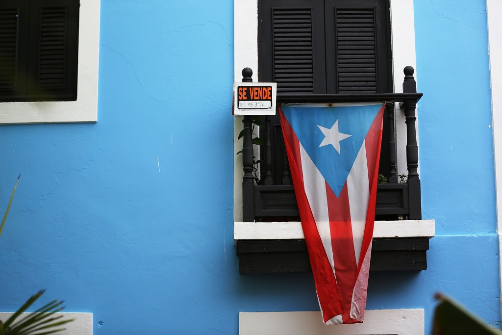 SAN JUAN, PUERTO RICO - JULY 01: A for sale sign is seen hanging from a balcony next to a Puerto Rican flag in Old San Juan as the island's residents deal with the government's $72 billion debt on July 1, 2015 in San Juan, Puerto Rico. Governor of Puerto Rico Alejandro García Padilla said in a speech recently that the people of Puerto Rico will have to make sacrifices and share the responsibilities to help pull the island out of debt. (Photo by Joe Raedle/Getty Images)