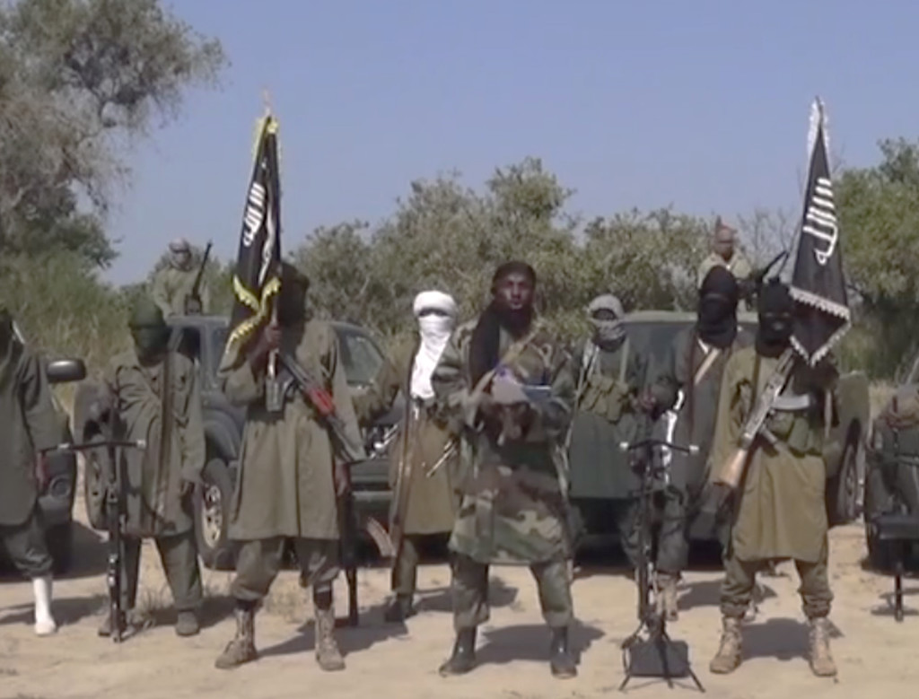 This Friday Oct. 31, 2014 image taken from video by Nigeria's Boko Haram terrorist network shows the leader of the Islamic extremist group, center.