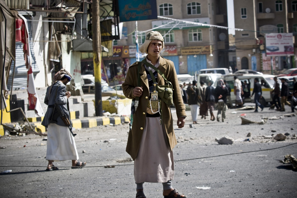 In this Tuesday, Jan. 20, 2015 file photo, Houthi Shiite Yemenis gather while guarding a street leading to the presidential palace in Sanaa, Yemen.