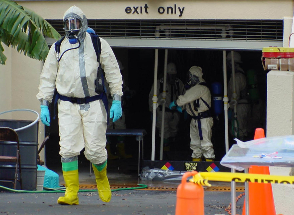 A member of a cleanup crew comprised of U.S. Coast Guard and U.S. Environmental Protection Agency agents walks from the American Media Inc., offices in Boca Raton, Fla., Thursday, Oct. 25, 2001. Investigators collected samples Thursday to begin decontaminating the headquarters of the tabloid publishing company shuttered by anthrax.