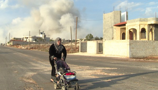 """In an image from 2012's """"Syria Behind the Lines,"""" an early documentary on the Syrian conflict, a woman pushes her stroller away from the blast, moments after a deadly airstrike hits the Sunni village of al-Bara."""