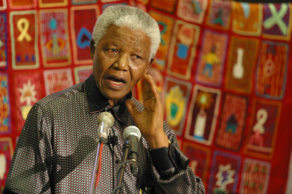 Former South African president Nelson Mandela in front of an AIDS quilt during a World AIDS Day function in Bloemfontein, South Africa, Sunday Dec. 1, 2002. Mandela said that people should stop blaming and criticizing the government for the research it is conducting into the safety of anti-retrovirals and urged greater acceptance of people with AIDS. (AP Photo/Benny Gool)