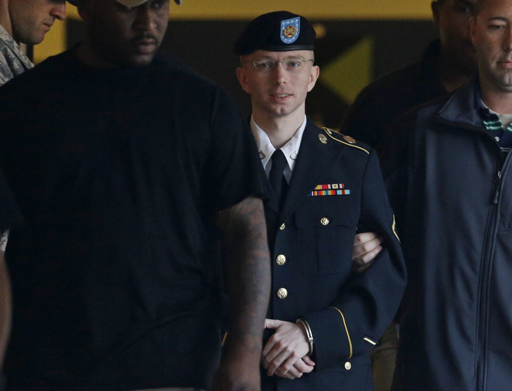 FILE - In this Monday, July 29, 2013, file photo, Army Pfc. Bradley Manning is escorted to a security vehicle outside of a courthouse in Fort Meade, Md. (AP Photo/Patrick Semansky, File)