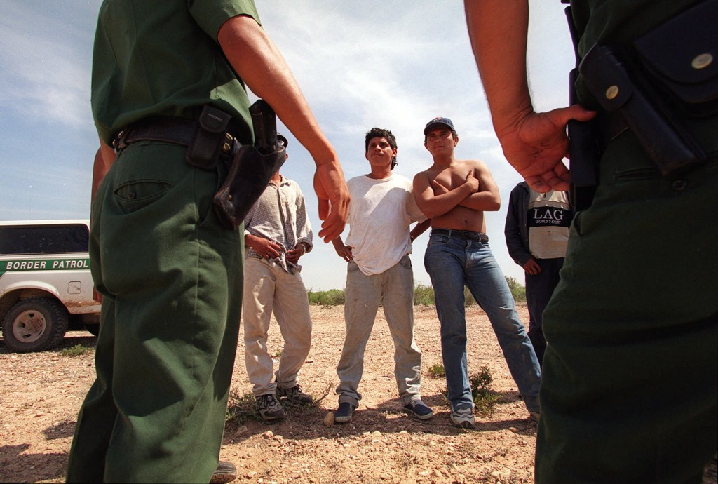 U.S. Border Patrol agents stand watch over a group of illegal immigrants after detaining them west of Laredo, Texas May 14, 2001. Mexico and the United States on Friday announced their most sweeping effort yet to reduce the deaths of migrants, including campaigns to warn migrants of risks, a crackdown on people-smugglers and experiments with border patrol agents firing pepper gas instead of bullets. (AP Photo/John Moore)