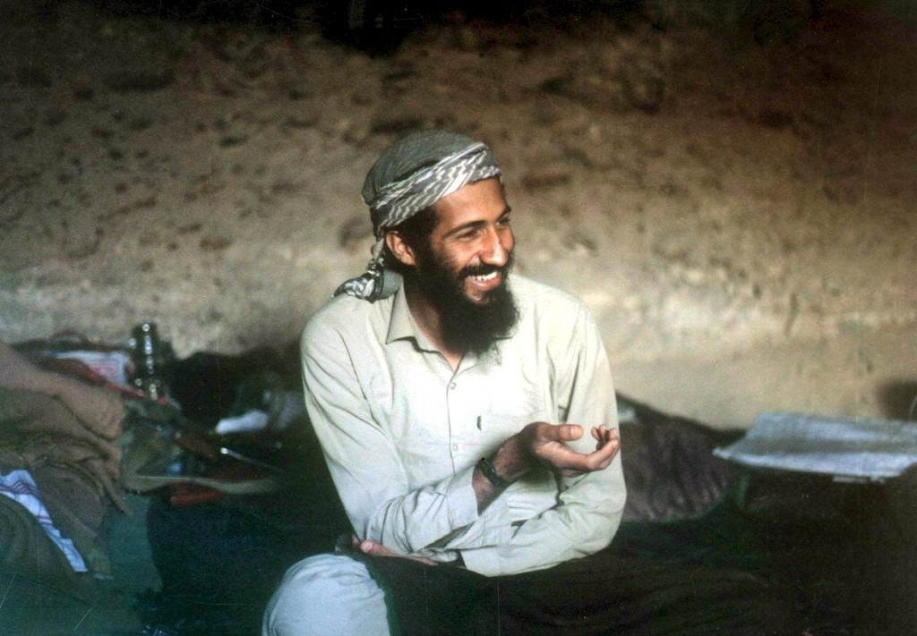 1988, Afghanistan --- Saudi-born billionaire Osama Bin Laden smilies as he sits in a cave in the Jalalabad region of Afghanistan.