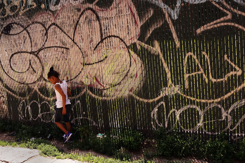 A child walks past graffiti in New York City in 2014. New Police Commissioner Bill Bratton has made combating graffiti one of his top priorities, as part of the Broken Windows theory of policing.