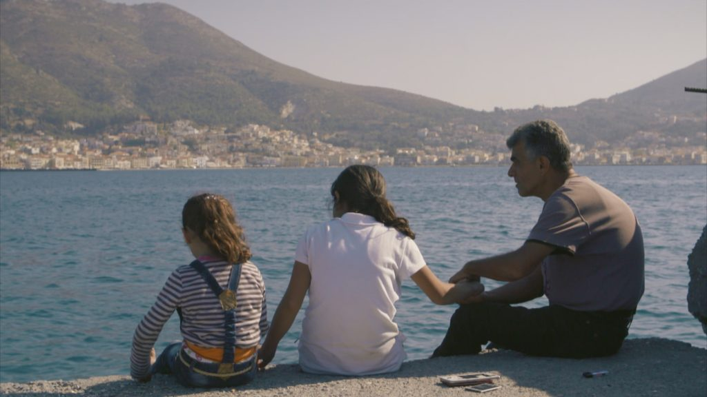 A family of Syrian refugees look out at the Mediterranean Sea after crossing from Turkey to Greece.