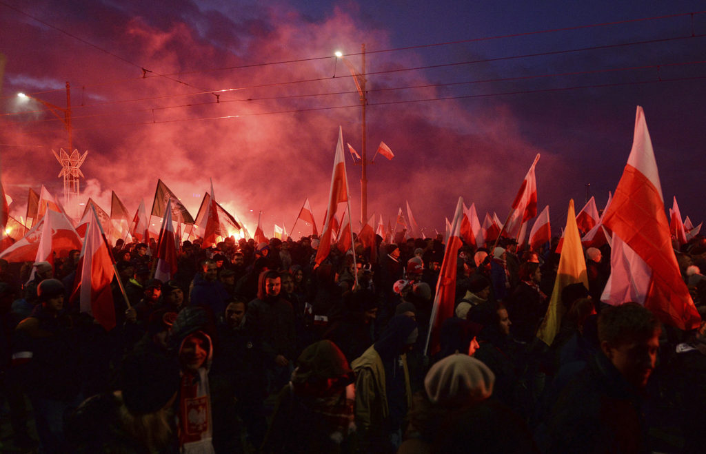 Demonstrators burn flares and wave flags during the annual march to commemorate Poland's Independence Day in Warsaw on Nov. 11, 2017. Thousands of nationalists marched, taking part in an event that was organized by far-right groups.