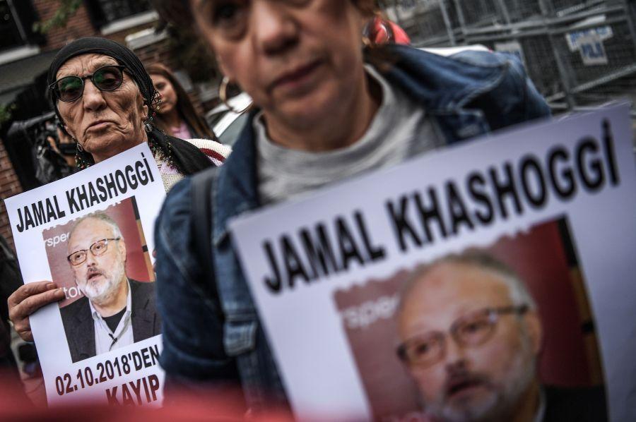 """Protesters hold a portrait of Jamal Khashoggi reading """"Jamal Khashoggi is missing since October 2."""""""