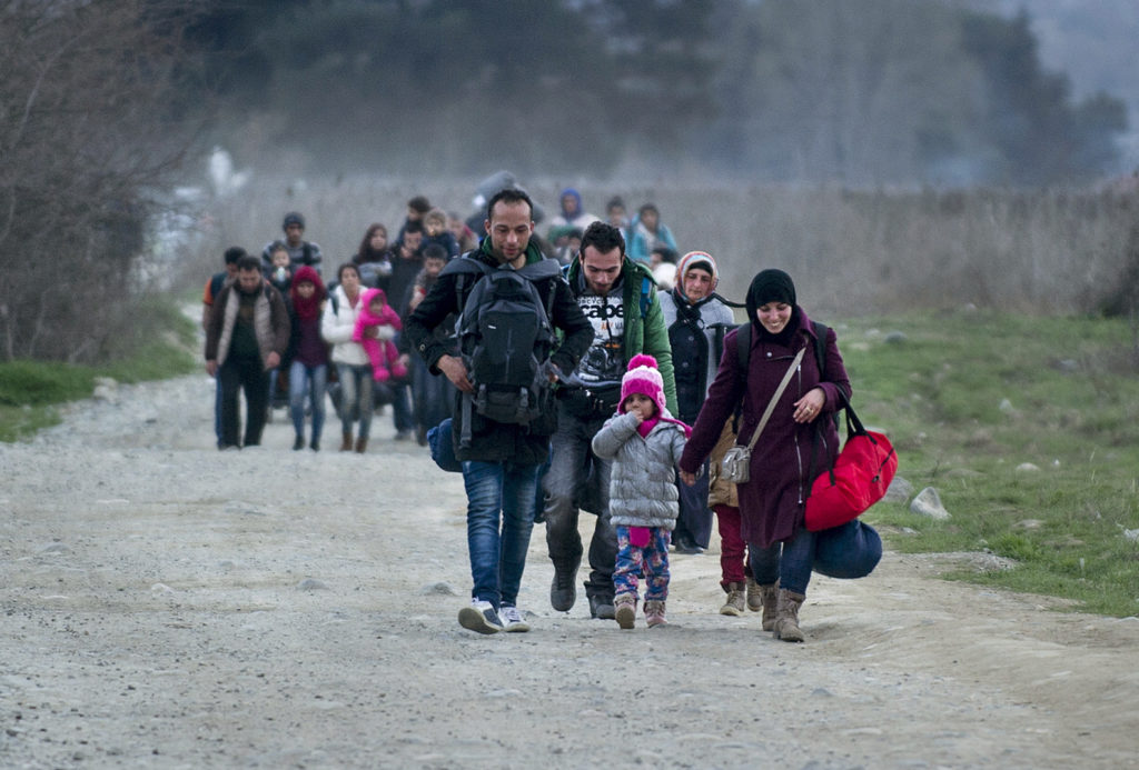 Migrants and refugees from Syria and Iraq cross the Greek-Macedonian border near the town of Gevgelija on February 23, 2016.