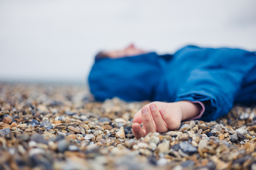 A woman faints on a beach.