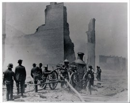 "1989 - Firefighters at fire of 1989. Firetruck (wagon) has hose in ditch also has large tank for water. Can see remains of burnt buildings up and down street. Grand Old Opera House! ""Rear of Grand Old Opera House, 1898, Park City Utah"""