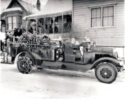 1932 - Judge James Don's Funeral Fire truck and flower-covered coffin of Judge James Don in back, parked in front of house. Blurred figures walk from house down steps. Taken in December, snow covers street. (firetruck that is Tooele Fireman Museum. Probably bought in 1926). James Don, a Scottish immigrant, worked as a printer, miner, postmaster, county treasurer, and until just before this death, city justice.