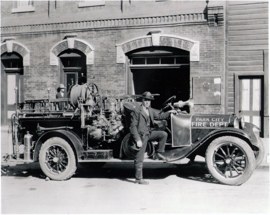 1930c Exterior of 528 Main Street with open garage doors, fire truck parked in front with William Berry, fire chief standing, foot on running board. One man in doorway of building. Frame bell tower at right. Brick building housed fire station, police station, city offices.