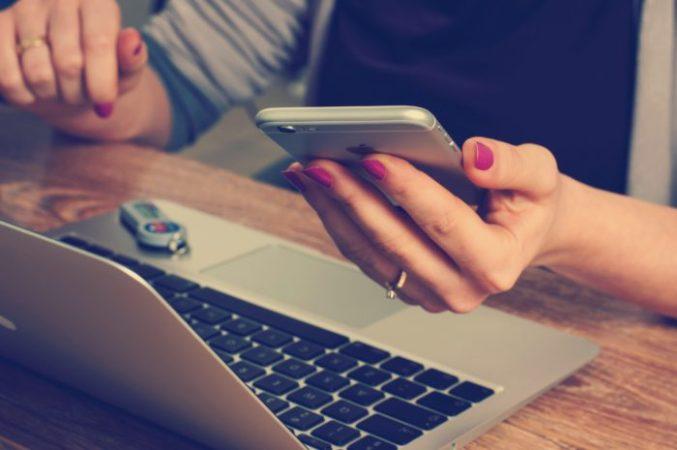 Das Bild zeigt eine Frau vor einem Laptop, die eine Authenticator-App nutzt. Bild: Unsplash/William Iven