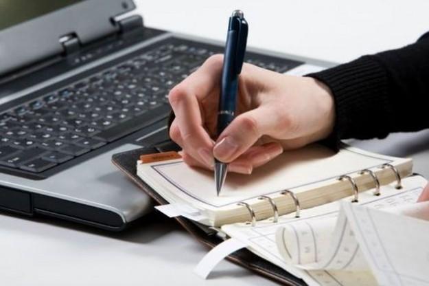 questa immagine mostra una persona che scrive appunti su un taccuino