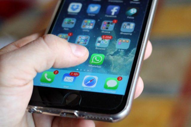 Mano che tiene un iPhone che sta pigiando l'icona di WhatsApp dalla Home