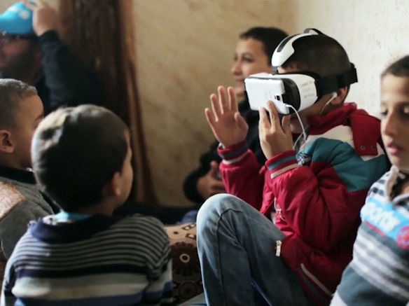 Children watching a virtual reality film in a refugee camp