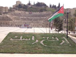 """The sign in the grass at the Roman Theater in Amman has the patriotic slogan: """"Hold your head high."""""""